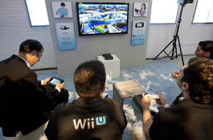 Photo -   FILE - In this Thursday, Sept. 13, 2012 file photo, people demonstrate the Nintendo's Wii U GamePad and console in New York. Nintendo seeks to shake up gaming again with the Wii U touchscreen controller. (AP Photo/Mark Lennihan, File)