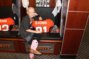 photo - Justin Blackmon fan Olivia Hamilton hangs out at Blackmon's locker before the Oklahoma State-Tulsa game. PHOTO BY BLAKE ROCKWELL, Founder of Special Spectators