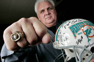 Photo - Former Miami Dolphins and University of Oklahoma (OU) football player Jim Riley shows his Super Bowl ring and his perfect season autographed helmet at his Edmond, Okla., home, December 10, 2005.  By Bryan Terry/The Oklahoman