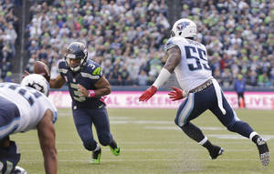 Photo - Seattle Seahawks quarterback Russell Wilson (3) recovers the ball after a Seahawks' fumble was touched by Tennessee Titans' Zach Brown and flicked back toward Wilson in the second half of an NFL football game, Sunday, Oct. 13, 2013, in Seattle. The Seahawks won 20-13. (AP Photo/Elaine Thompson)
