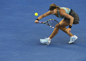 Photo - Eugenie Bouchard of Canada makes a forehand return to Casey Dellacqua of Australia during their fourth round match at the Australian Open tennis championship in Melbourne, Australia, Sunday, Jan. 19, 2014.(AP Photo/Aijaz Rahi)
