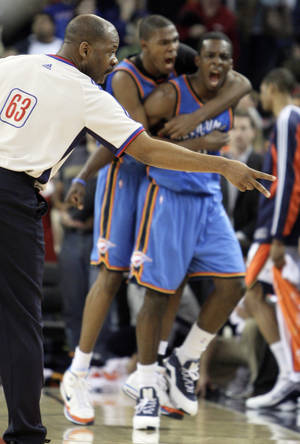 Photo - Referee Derek Richardson counts the last two points of the game as Oklahoma City Thunder's Kevin Durant, center, and  Jeff  Green celebrate  Green's game-winning basket against the Golden State Warriors during the fourth period of an NBA basketball game on Wednesday in Oakland, Calif. (AP Photo/Ben Margot)