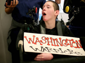 photo - With a Washington Warriors sign set up in front of him, Chris Schatz, watches the Bethany and Washington high school football teams compete during the Goodwill Games at The Children&#039;s Center in Bethany on Thursday, September 15, 2011. Photo by John Clanton, The Oklahoman ORG XMIT: KOD