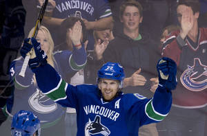 Photo - Vancouver Canucks left wing Daniel Sedin (22) celebrates his goal during the second period of NHL hockey action against the Edmonton Oilers in Vancouver, British Columbia, Saturday, Oct. 5, 2013. (AP Photo/The Canadian Press, Jonathan Hayward)