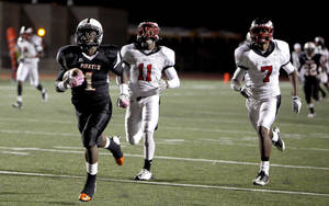 Photo - Putnam City's Casey Curtis scores a touchdown as Del City's Larry Long (11) and Jerell Jeter (7) chase him during the high school football game between Putnam City and Del City in Oklahoma City,  Thursday, Sept. 29, 2011. Photo by Sarah Phipps, The Oklahoman