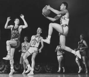 "Photo - BASKETBALL / ALL-COLLEGE TOURNAMENT / OKLAHOMA CITY / OKLAHOMA A&M / IDAHO / BASKETBALL TOURNAMENT / 1951:  ""The camera froze some lively action here Saturday night as Oklahoma A&M shot its way to third place in the All-College by trimming Idaho.  Here the Cowboys' Don Johnson takes off as if bouncing from a springboard for an underbasket shot over the guarding efforts of Harlan Melton, left.  After feeding Johnson the Pokes' Harold Rogers (30) puts some body English on his teammate's effort.  Johnson is a senior from Chickasha.""   Staff photo by Bill Burns.  Original photo dated 12/29/1951.  Published on 12/30/1951 in The Daily Oklahoman."