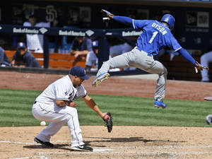 Photo - Kansas City Royals' Jarrod Dyson sails through the air while scoring over San Diego Padres pitcher Hector Ambriz after a passed ball during the eighth inning of a baseball game Wednesday, May 7, 2014, in San Diego.  (AP Photo/Lenny Ignelzi)