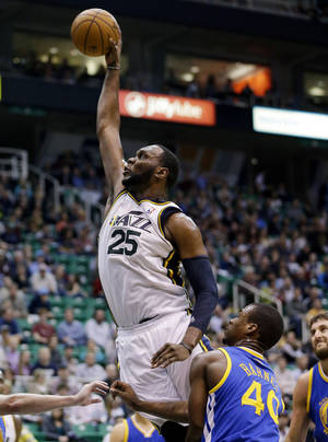 Photo - Utah Jazz's Al Jefferson (25) goes for a dunk over  Golden State Warriors' Harrison Barnes (40) in the third quarter of an NBA basketball game Tuesday, Feb. 19, 2013, in Salt Lake City. The Jazz defeated the Warriors 115-101. (AP Photo/Rick Bowmer)