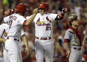 Photo - St. Louis Cardinals' Allen Craig, center, is congratulated by Matt Carpenter, left, after hitting a grand slam as Cincinnati Reds catcher Devin Mesoraco, right, stands by during the seventh inning of a baseball game, Monday, Aug. 26, 2013, in St. Louis. (AP Photo/Jeff Roberson)