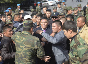 Photo -   Guards protecting government headquarters, detain Kamchibek Tashiyev, center, surrounded by supporters, after he scaled over a fence surrounding government headquarters in downtown Bishkek, Kyrgyz capital on Wednesday, Oct. 3, 2012. Around 1,000 people gathered in the center of the city for a rally, organized by nationalist politicians Sapar Zhaparov and Kamchibek Tashiyev, ostensibly to demand the nationalization of a controversial gold mine in the east of the Central Asian nation. Police officers protecting the government building, known as the White House, used dogs and smoke bombs to disperse a group of young men who attempted to scale the gates. (AP Photo/ Abylay Saralayev)