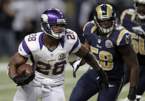 Photo - Minnesota Vikings running back Adrian Peterson, left, runs past St. Louis Rams outside linebacker Jo-Lonn Dunbar on his way to a 52-yard gain during the fourth quarter of an NFL football game Sunday, Dec. 16, 2012, in St. Louis. (AP Photo/Tom Gannam)