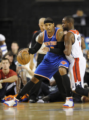 Photo - New York Knicks forward Carmelo Anthony, left, drives against Washington Wizards forward Martell Webster (9) during the first half of an NBA preseason basketball game, Thursday, Oct. 17, 2013, in Baltimore. (AP Photo/Nick Wass)