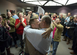 Photo - Chris Serrano, left, and Clifton Webb kiss after being married, as people wait in line to get licenses outside of the marriage division of the Salt Lake County Clerk's Office in Salt Lake City, Friday, Dec. 20, 2013.  A federal judge ruled on Friday that Utah's ban on same-sex marriage is unconstitutional. (AP Photo/Kim Raff)