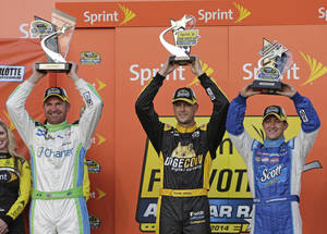 Photo - Clint Bowyer, left, Josh Wise, center, and AJ Allmendinger, right, raise their trophies after the NASCAR Sprint Showdown auto race at Charlotte Motor Speedway in Concord, N.C., Friday, May 16, 2014. All three gained a spot in Saturday's All-Star race with Bowyer winning the race, Allmendinger finishing second, and Josh Wise being selected by a fan vote. (AP Photo/Chuck Burton)