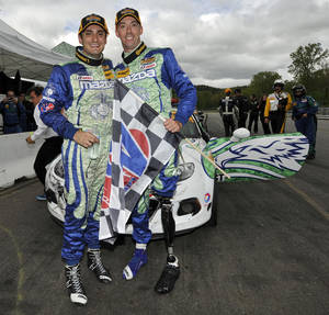 Photo - In this photo provided by LAT Photo USA for IMSA,  U.S. Marine Staff Sgt. Liam Dwyer, right, and Tom Long left, pose for a photo after winning the Northeast Grand Prix at Lime Rock Park, Saturday, May 24, 2014, in Lakeville, Conn. Dwyer always knew that despite losing much of his left leg in combat, he could find racing success if he got the chance. That came Saturday when Dwyer teamed with Tom Long to win the ISMA Continental Tire SportsCar Challenge event Saturday. (AP Photo/Scott R LePage, LAT Photo USA for IMSA)