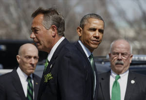 Photo - President Barack Obama and House Speaker John Boehner of Ohio part ways following a St. Patrick's Day luncheon on Capitol Hill in Washington, Friday, March 14, 2014. The political rivals came together to host a gathering for Taoiseach Enda Kenny of Ireland. They are flanked by House Sergeant at Arms Paul Irving, left, and Senate Sergeant at Arms Terrance Gainer.  (AP Photo/J. Scott Applewhite)