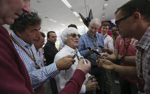 Photo - Bernie Ecclestone, center, president and CEO of Formula One Management, center, answers to reporters in the newsroom ahead the the Bahrain Formula One Grand Prix at the Bahrain International Circuit in Sakhir, Bahrain, Sunday, April 6, 2014. (AP Photo/Luca Bruno)