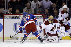 Photo - New York Rangers' Ryan McDonagh, left, scores the winning goal past Phoenix Coyotes goalie Thomas Greiss, center, while Derek Morris looks on in overtime at the NHL hockey game, Monday, March 24, 2014, in New York. The Rangers defeated the Coyotes in overtime 4-3. (AP Photo/Seth Wenig)
