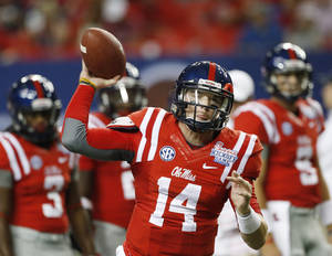 Photo - Mississippi quarterback Bo Wallace (14) warms up before the first half of an NCAA college football game against Boise State Thursday, Aug. 28, 2014, in Atlanta. (AP Photo/John Bazemore)