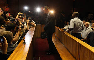 Photo - In this photo taken Friday, Feb. 22, 2013, Olympic athlete Oscar Pistorius appears in court during his bail hearing in Pretoria, South Africa, for the shooting death of his girlfriend Reeva Steenkamp. A spokeswoman for Oscar Pistorius says he has reported to authorities under the bail terms in the murder case against him in Preoria, Monday, Feb. 25, 2013. AP Photo/Themba Hadebe)