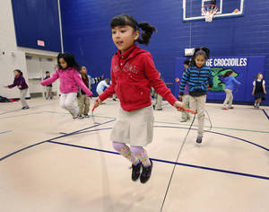 Photo - Second-grader Yamilet Soliz jumps rope with fellow students during P.E. class at Coolidge Elementary School.