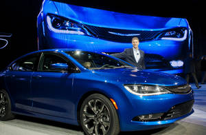 Photo - Chrysler President and CEO Al Gardner poses with a newly unveiled 2015 Chrysler 200 sedan, Monday, Jan. 13, 2014, at the North American International Auto Show in Detroit, Mich. (AP Photo/Tony Ding)