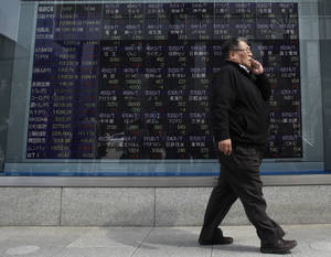 Photo - A man talking on a mobile phone walks past an electronic board showing stock prices outside a securities company in Tokyo Thursday, March 7, 2013. Japan's Nikkei 225 index topped 12,000 for the first time in more than four years, but stock markets elsewhere in Asia flagged following Wall Street's eye-popping performance this week. (AP Photo/Shuji Kajiyama)