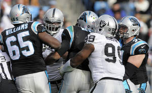 Photo - Oakland Raiders' Lamarr Houston, right, holds back Carolina Panthers' Cam Newton, center, as Newton chases after Oakland Raiders' Tommy Kelly, back left, during the first half of an NFL football game in Charlotte, N.C., Sunday, Dec. 23, 2012. (AP Photo/Mike McCarn)
