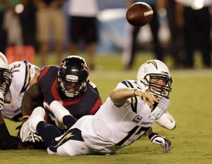 Photo - San Diego Chargers quarterback Philip Rivers, right, throws under pressure from Houston Texans outside linebacker Whitney Mercilus during the first half of an NFL football game Monday, Sept. 9, 2013, in San Diego. (AP Photo/Gregory Bull)