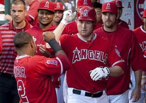 Photo -   Los Angeles Angels left fielder Mark Trumbo celebrates with shortstop Erick Aybar, left, after Trumbo's solo home run against the Seattle Mariners in the second inning of a baseball game in Anaheim, Calif., Tuesday, June 5, 2012. (AP Photo/Grant Hindsley)