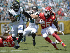 Photo - Kansas City Chiefs running back Jamaal Charles (25) looks for a way past Jacksonville Jaguars free safety John Cyprien (37) during the first half of an NFL football game in Jacksonville, Fla., Sunday, Sept. 8, 2013.(AP Photo/Phelan M. Ebenhack)