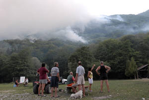 Photo -   Bosnians watch a forest fire at Boracko Lake near the town of Konjic, 50 km south of Sarajevo in Bosnia, Tuesday Aug. 21. 2012. Citizens and tourists began evacuating from Boracko Lake as wildfires reached the houses and tourist camps in the area. (AP Photo/Sulejman Omerbasic)