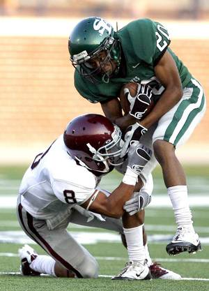 photo - Edmond Santa Fe's Cameron Westbrook tries to get by Edmond Memorial's Devin Cossman during the high school football game between Edmond Santa Fe and Edmond Memorial at Wantland Stadium in Edmond, Okla.,  Friday, Sept. 2, 2011. Photo by Sarah Phipps, The Oklahoman