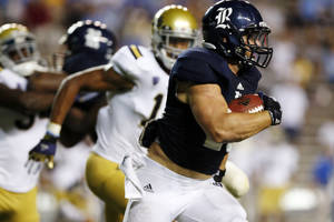 Photo -   Rice running back Turner Petersen (26) carries the ball during the second half of an NCAA college football game against UCLA, Thursday, Aug. 30, 2012, in Houston. UCLA won 49-24. (AP Photo/Eric Kayne)
