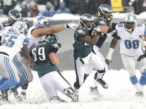 Photo - Philadelphia Eagles' LeSean McCoy, center, breaks away from the line of scrimmage en route to his second touchdown run during an NFL football game against the Detroit Lions, Sunday, Dec. 8, 2013, in Philadelphia. (AP Photo/Philadelphia Inquirer, Ron Cortes) PHILADELPHIA OUT; NEWARK, N.J. OUT; TV OUT; MAGAZINES OUT