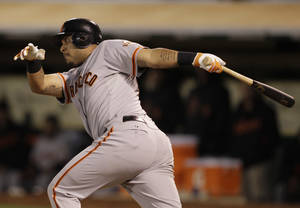 Photo -   San Francisco Giants' Hector Sanchez hits an RBI single against the =ok during the ninth inning of their interleague baseball game in Oakland, Calif., Friday, June 22, 2012. (AP Photo/Eric Risberg)