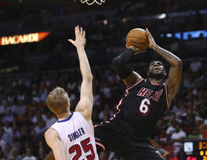 Photo - Detroit Pistons' Kyle Singler (25) tries to block Miami Heat's LeBron James (6) during the first half of a NBA basketball game in Miami, Monday, Feb. 3, 2014. (AP Photo/J Pat Carter)