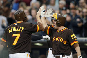 Photo - San Diego Padres' Chase Headley, left, high fives with teammate Jedd Gyorko after scoring on a two-run home run by Yonder Alonso in the first inning of a baseball game against the Chicago Cubs, Friday, May 23, 2014, in San Diego. (AP Photo/Don Boomer)