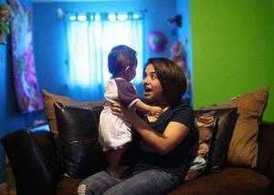photo - Adriana Mireles Robles, 18, holds her nephew, Noel Ramirez, inside her home in Oklahoma City. Robles, 18, came here with her family from Mexico when she was 2 years old. Her family has applied for permanent residency but it has been pending for 16 years. <strong>Adam Wisneski - Tulsa World</strong>