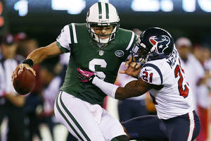 Photo -   Houston Texans defensive back Brice McCain (21) sacks New York Jets quarterback Mark Sanchez (6) during the second half of an NFL football game Monday, Oct. 8, 2012, in East Rutherford, N.J. The Texans won the game 23-17. (AP Photo/Julio Cortez)