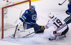 Photo - Chicago Blackhawks center Jonathan Toews (19) puts a shot past Vancouver Canucks goalie Roberto Luongo (1)during the second period of NHL action in Vancouver, British Columbia Wednesday, Jan. 29, 2014. (AP Photo/The Canadian Press, Jonathan Hayward)