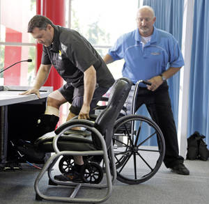 Photo - NASCAR driver and team co-owner Tony Stewart, left, arrives in a wheelchair assisted by Josh Katz, right, before a news conference at Stewart-Haas Racing's headquarters in Kannapolis, N.C., Tuesday, Sept. 3, 2013. (AP Photo/Chuck Burton)