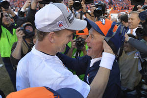 Photo - Denver Broncos quarterback Peyton Manning, left, celebrates with Denver Broncos head coach John Fox after the AFC Championship NFL playoff football game against the New England Patriots in Denver, Sunday, Jan. 19, 2014. The Broncos defeated the Patriots 26-16 to advance to the Super Bowl. (AP Photo/Jack Dempsey)