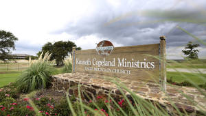 Photo - This Aug. 27, 2013, photo shows a sign at the entrance of the Kenneth Copeland Ministries Eagle Mountain Church, in Newark, Texas. The Texas megachurch was linked to at least 21 cases of measles and tried to combat the outbreak by hosting vaccination clinics, officials said. (AP Photo/LM Otero) <strong>LM Otero</strong>