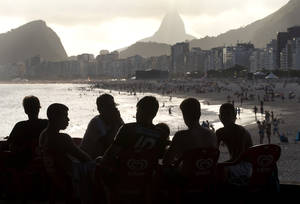 Photo - Men are silhouetted against Copacabana beach in Rio de Janeiro, Brazil, Thursday, Dec. 26, 2013. Sports fans on a budget may want to bypass the World Cup and wait until the 2016 Olympics before making a trip to Brazil, especially considering estimated hotel rates in Rio de Janeiro during both events. Tourists visiting the city for the 2014 World Cup could end up paying three times more for hotels compared to those coming for the Olympics two years later, according to recent industry studies and research by The Associated Press. (AP Photo/Silvia Izquierdo)