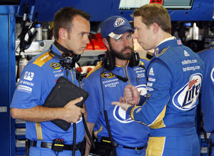 photo -   FILE - This Nov. 3, 2012 file photo shows crew chief Paul Wolfe, left, and a fellow crew member talking with Brad Keselowski, right, following a practice session for a NASCAR Sprint Cup Series race at Texas Motor Speedway in Fort Worth, Texas. Wolfe wasn't interested in working with Brad Keselowski when the driver first approached him about a potential pairing. He's now got Keselowski one race away from a Sprint Cup Series championship. (AP Photo/Tim Sharp, File)