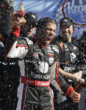 Photo - Driver Darrell Wallace Jr. celebrates in Victory Lane winning the NASCAR Truck Series auto race at  Martinsville Speedway in Martinsville, Va., Saturday, Oct. 26, 2013. (AP Photo/Steve Helber)