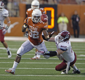 Photo - Texas running back Johnathan Gray (32) bobbles a pass before his catch of a David Ash pass while defended by New Mexico State linebacker Clint Barnard during the second quarter of an NCAA college football game Saturday Aug. 31, 2013, in Austin, Texas. (AP Photo/Michael Thomas)