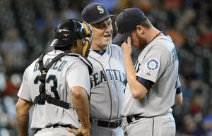 Photo - Seattle Mariners pitching coach Carl Willis, center, talks with relief pitcher Charlie Furbush, right, and catcher Henry Blanco after Furbush gave up the only two runs for the Houston Astros in the eighth inning of a baseball game Sunday, Sept. 1, 2013, in Houston. The Astros won 2-0. (AP Photo/Pat Sullivan)