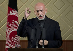 """Photo - Afghan President Hamid Karzai gestures during a ceremony at Kabul University in Kabul, Afghanistan, Thursday, May 9, 2013. Karzai said he is ready to let the U.S. have nine bases in the country after the 2014 combat troop pullout, but wants Washington's """"security and economic guarantees"""" first.  (AP Photo/Anja Niedringhaus)"""
